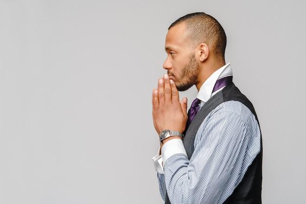 Afroamerikanermann, der hände im gebet hält