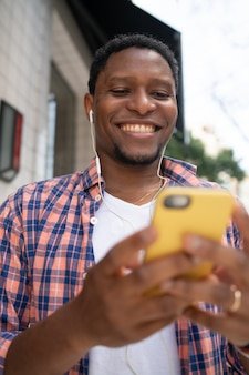 Afroamerikanermann, der lächelt und sein handy benutzt, während er draußen auf der straße steht