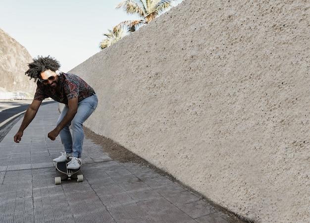 Afroamerikanermann, der longboard auf der straße mit palmen im hintergrund reitet - fokus auf gesicht
