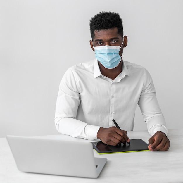 Afroamerikanermann, der medizinische maske bei der arbeit trägt