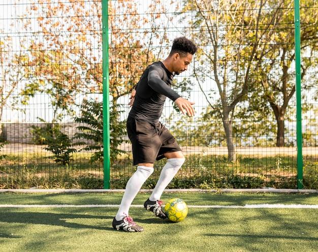 Afroamerikanermann, der mit einem fußball spielt