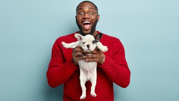 Afroamerikanermann, der roten pullover hält, der hund hält