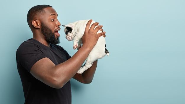 Afroamerikanermann, der schwarzen t-shirt hält hund hält