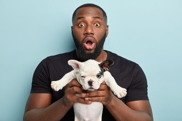 Afroamerikanermann, der schwarzes t-shirt trägt und kleinen hund hält