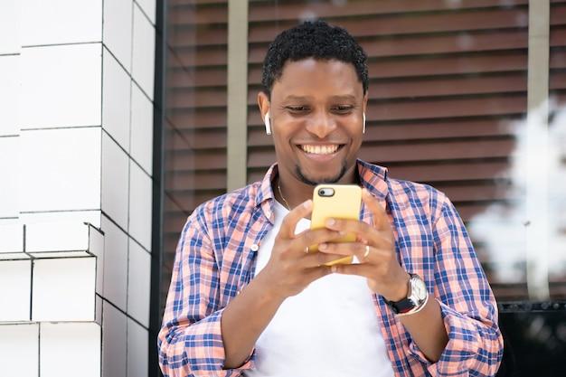 Afroamerikanermann, der sein handy benutzt, während er an einem schaufenster auf der straße sitzt. stadtkonzept.