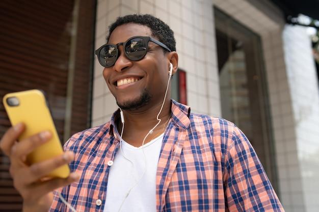 Afroamerikanermann, der sein mobiltelefon beim gehen im freien auf der straße verwendet. stadtkonzept.