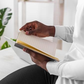 Afroamerikanermann, der seine notizen nahaufnahme liest