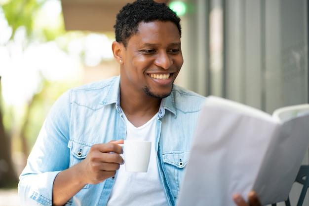 Afroamerikanermann, der sich entspannt und ein buch liest, während er an einem kaffeehaus sitzt