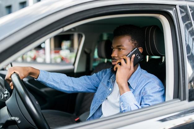 Afroamerikanermann, der smartphone verwendet, das mobilfunkanruf während der fahrzeit im lieblingsluxusauto macht.