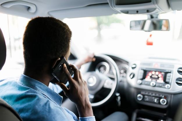 Afroamerikanermann, der smartphone verwendet, das mobilfunkanruf während der fahrzeit im luxusauto macht.
