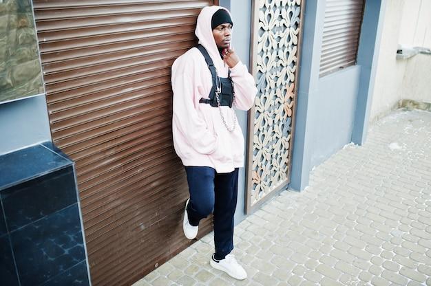Afroamerikanermann der stilvollen städtischen art im rosa hoodie aufgeworfen. afro-rapper-typ.