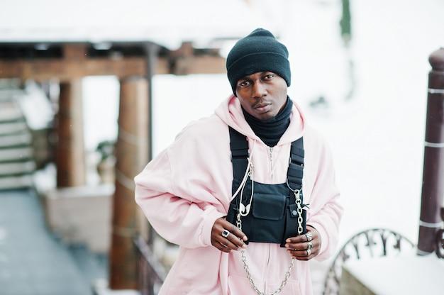 Afroamerikanermann der stilvollen städtischen art im rosa hoodie warf am wintertag auf.