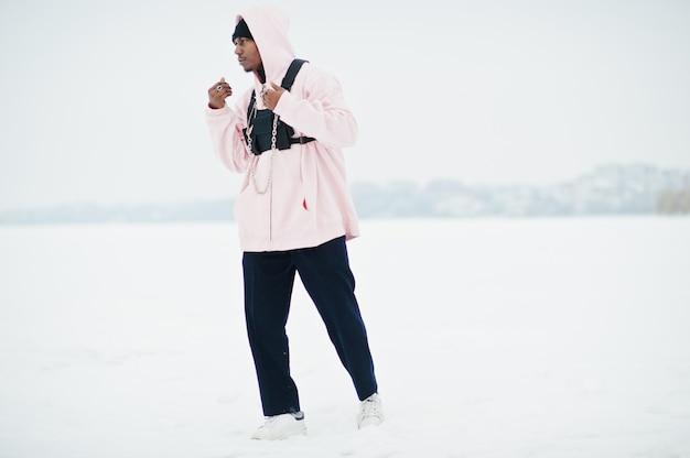 Afroamerikanermann der stilvollen städtischen art im rosa hoodie warf in gefrorenem see im winter auf.