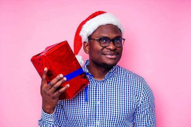 Afroamerikanermann, der stilvolles kariertes hemd großes lächeln in weihnachtsmütze mit geschenkbox auf rosa hintergrundstudio trägt