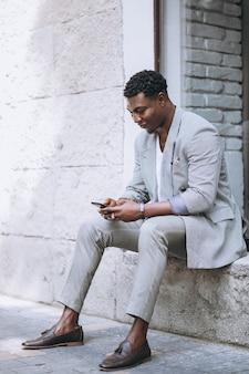 Afroamerikanermann, der telefon verwendet