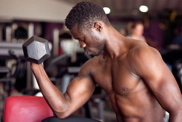 Afroamerikanermann, der übungen mit hanteln in einer turnhalle macht