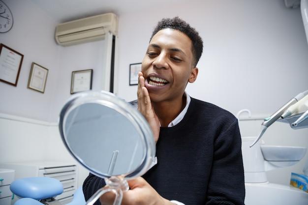 Afroamerikanermann, der unter zahnschmerzen beim schauen in den spiegel und beschweren während des besuchs zum berufszahnarzt leidet