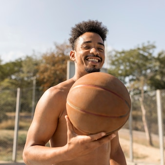 Afroamerikanermann der vorderansicht, der basketball hemdlos spielt