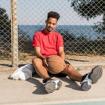 Afroamerikanermann der vorderansicht, der eine pause nach einem basketballspiel macht