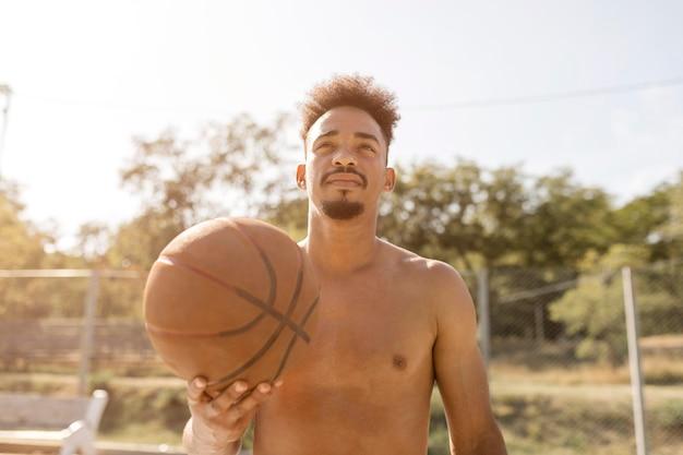 Afroamerikanermann der vorderansicht, der mit einem basketball spielt