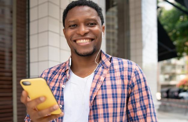 Afroamerikanermann, der während des mobiltelefons draußen auf der straße lächelt. stadtkonzept.