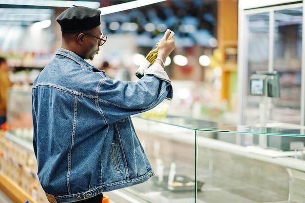 Afroamerikanermann, der weinflasche hält