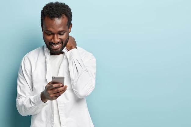 Afroamerikanermann, der weißes hemd hält telefon hält