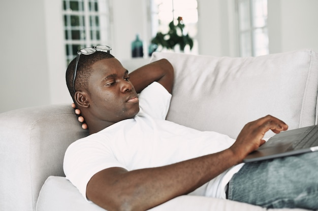 Afroamerikanermann, der zu hause freiberuflicher laptop arbeitet