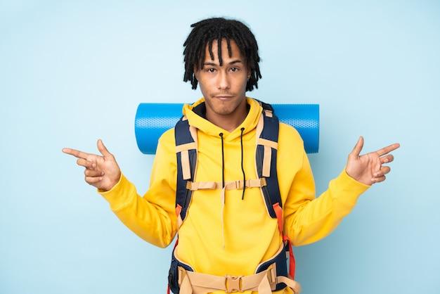 Afroamerikanermann des jungen bergsteigers mit einem großen rucksack, der auf einem blau lokalisiert ist, das auf die seitenteile zeigt, die zweifel haben