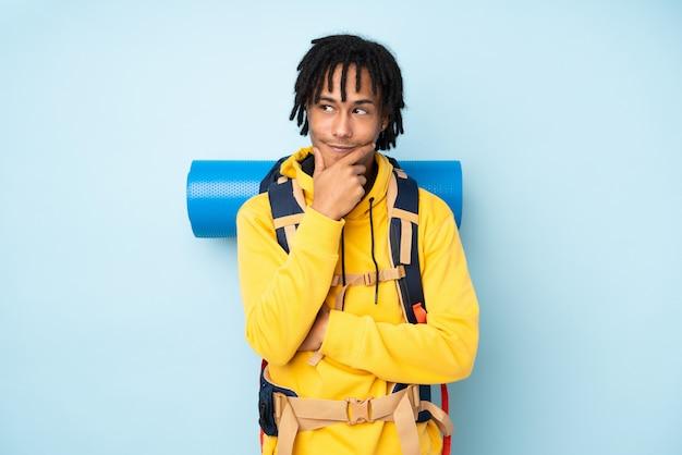 Afroamerikanermann des jungen bergsteigers mit einem großen rucksack lokalisiert auf einem blau, das eine idee denkt