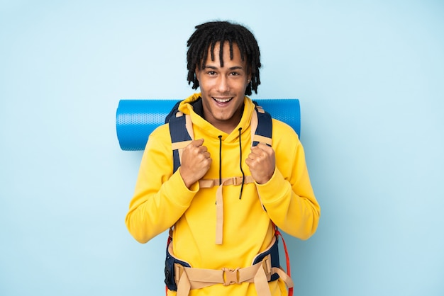 Afroamerikanermann des jungen bergsteigers mit einem großen rucksack lokalisiert auf einem blau, das einen sieg feiert