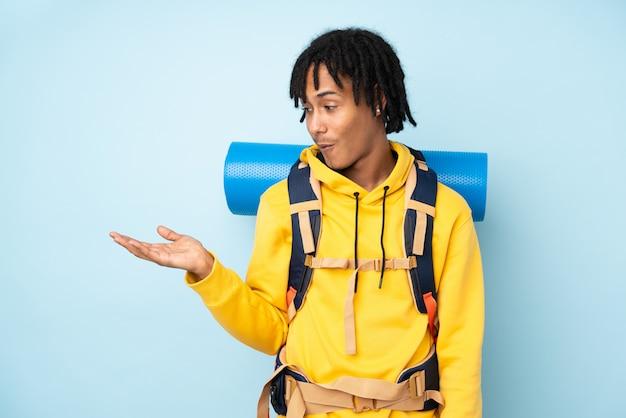 Afroamerikanermann des jungen bergsteigers mit einem großen rucksack lokalisiert auf einem blauen haltekopyspace imaginär auf der handfläche