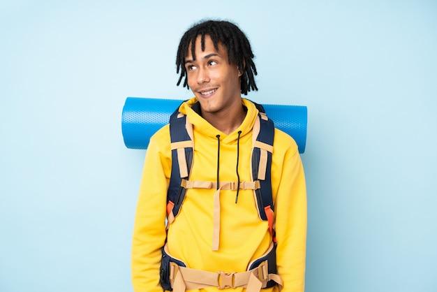 Afroamerikanermann des jungen bergsteigers mit einem großen rucksack lokalisiert auf einem blauen lachen und aufblicken