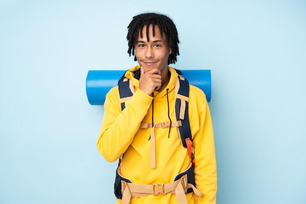 Afroamerikanermann des jungen bergsteigers mit einem großen rucksack lokalisiert auf einem blauen lachen