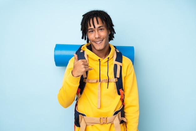 Afroamerikanermann des jungen bergsteigers mit einem großen rucksack lokalisiert auf einer blauen, die telefongeste macht