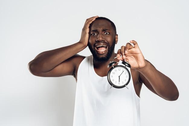 Afroamerikanermann hält kopf mit wecker