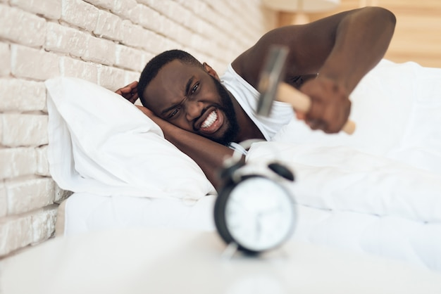 Afroamerikanermann hämmert wecker. aufwachen.