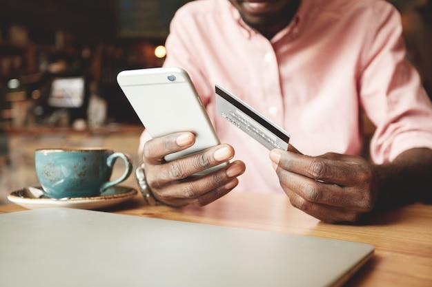 Afroamerikanermann im freizeithemd, der mit kreditkarte online zahlt, während er bestellungen macht