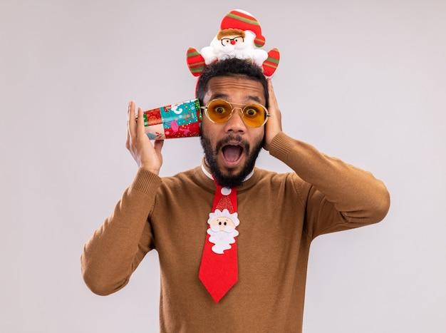 Afroamerikanermann in braunem pullover und weihnachtsmannrand auf kopf mit lustiger roter krawatte, die bunte pappbecher über ohr hält, das überrascht steht, über weißem hintergrund steht