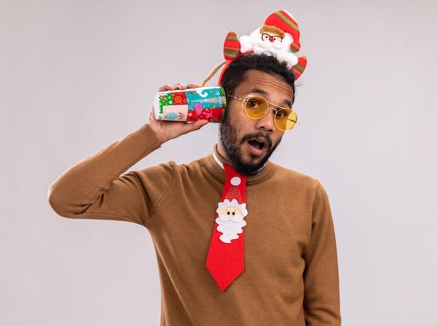 Afroamerikanermann in braunem pullover und weihnachtsmannrand auf kopf mit lustiger roter krawatte, die bunten pappbecher über seinem ohr hält und überrascht steht über weißem hintergrund