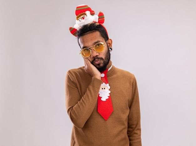 Afroamerikanermann in braunem pullover und weihnachtsmannrand auf kopf mit lustiger roter krawatte, die kamera mit schüchternem lächeln auf gesicht steht, das über weißem hintergrund steht