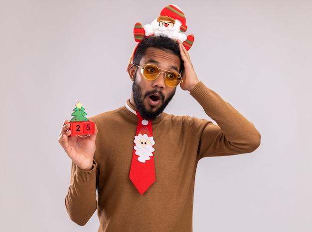 Afroamerikanermann in braunem pullover und weihnachtsmannrand auf kopf mit lustiger roter krawatte, die spielzeugwürfel mit datum fünfundzwanzig betrachtet kamera betrachtet, die mit hand auf seinem kopf verwechselt wird, der über weißem hintergrund steht