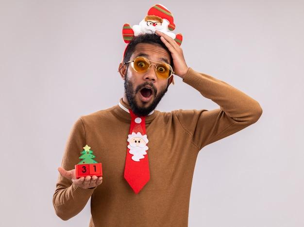 Afroamerikanermann in braunem pullover und weihnachtsmannrand auf kopf mit lustiger roter krawatte, die spielzeugwürfel mit neujahrsdatum betrachtet, das kamera betrachtet und überrascht über weißem hintergrund steht