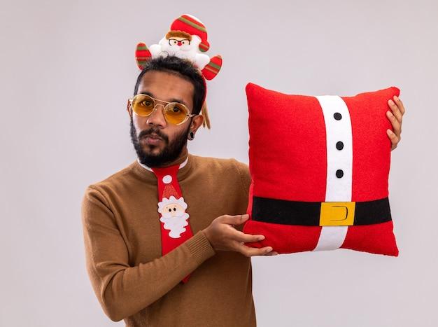 Afroamerikanermann in braunem pullover und weihnachtsmannrand auf kopf mit lustiger roter krawatte, die weihnachtskissen hält, überrascht über weißer wand stehend