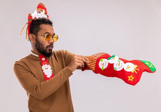 Afroamerikanermann in braunem pullover und weihnachtsmannrand auf kopf mit lustiger roter krawatte, die weihnachtsstrumpf hält, der sie betrachtet, der über weißer wand überrascht steht
