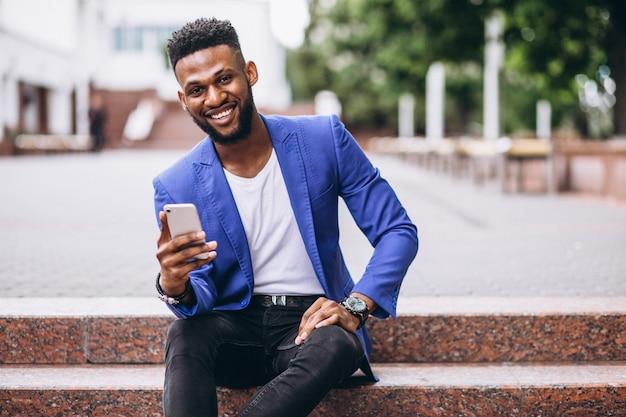 Afroamerikanermann in der blauen jacke unter verwendung des telefons
