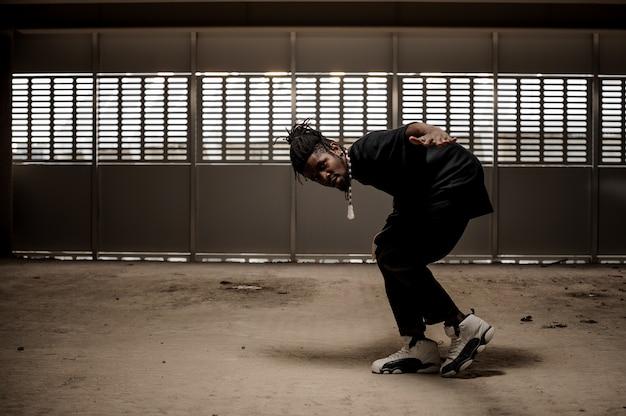 Afroamerikanermann in der schwarzen kleidung im tanz