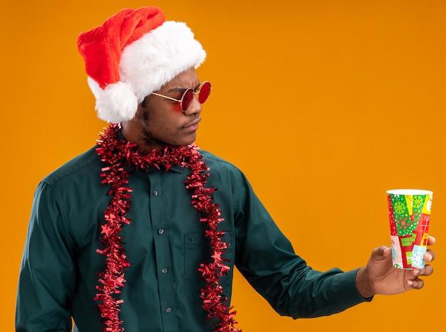 Afroamerikanermann in der weihnachtsmannmütze mit der girlande, die sonnenbrille hält, die bunten pappbecher hält, der sie mit ernstem gesicht betrachtet, das über orange wand steht