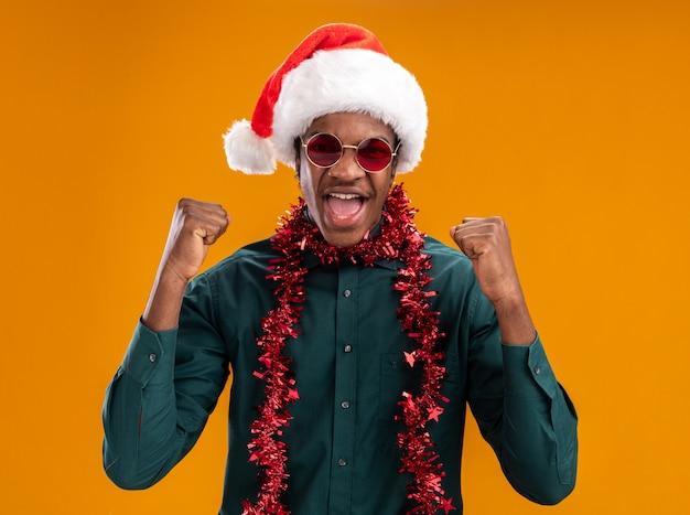 Afroamerikanermann in der weihnachtsmannmütze mit girlande, die glückliche und aufgeregte geballte fäuste der brille trägt, die über orange wand stehen