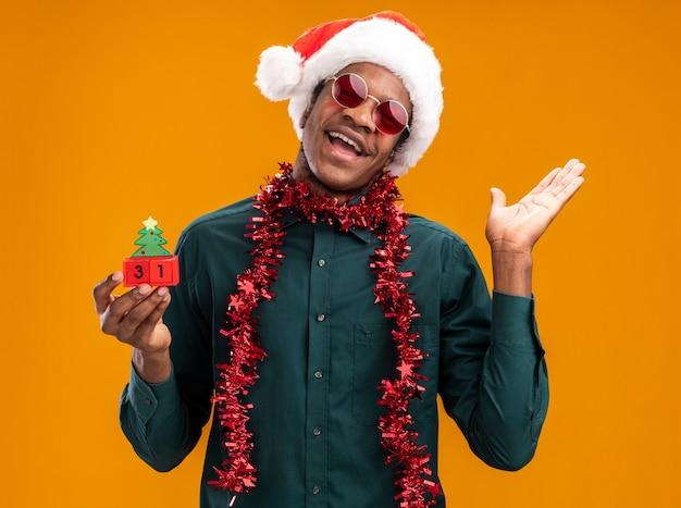 Afroamerikanermann in der weihnachtsmannmütze mit girlande, die sonnenbrille hält, die spielzeugwürfel mit neujahrsdatum glücklich und fröhlich mit erhöhtem arm hält, der über orange wand steht